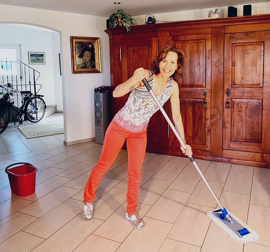 Regula von Huben putzt mit Mop den Feinsteinzeugboden in ihrem Wohnzimmer